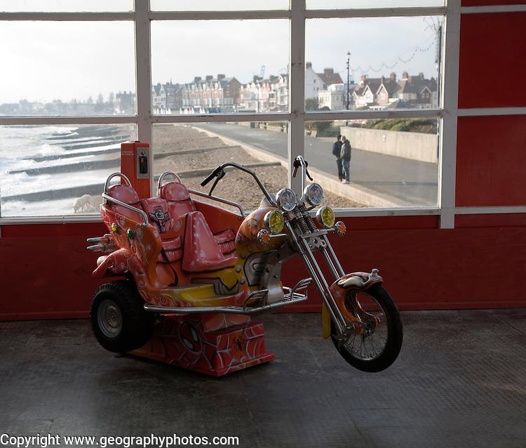 Children's motorbike ride in the pier amusements arcade in winter, Felixstowe, Suffolk, England