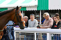Racegoers study the horses in the Parade Ring during Afternoon Racing at Salisbury Racecourse on 16th May 2019