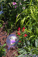 Glass globe in garden of Echinacea, red salvia, daylilies, pulmonaria, gazing ball