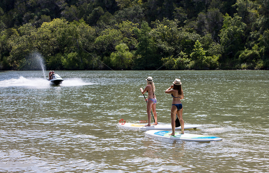 Two fit females in bikinis on stand up paddle boards surfing together on Lake Travis as jet skies race by for summer time fun in Austin, Texas.