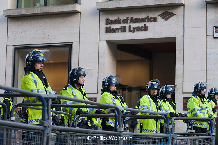 Police guard Bank of America Merrill Lynch during a National Campaign against Fees and Cuts march through the City of London.