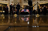 People pay their respects near the flag draped casket of former President George H.W. Bush in the Capitol Rotunda in Washington, DC, December 3, 2018. - The body of the late former President George H.W. Bush will travel from Houston to Washington, where he will lie in state at the US Capitol through Wednesday morning. Bush, who died on November 30, will return to Houston for his funeral on Thursday. (Photo by Brendan Smialowski / POOL / AFP)