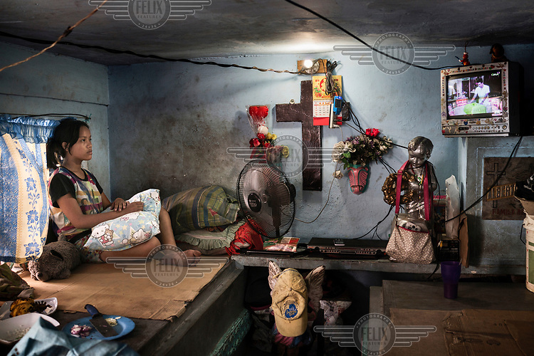 Lorgen Lozano, 14, watches soap operas on TV in the home her family built on tombs in Manila North Cemetery.  Manila North Cemetery is home to thousands of 'informal settlers' who have built shacks using in and around the mausoleums, crypts and tombs. In comparison to the city's dangerous shantytowns the cemetery is relatively quiet and safe. However, water must be collected from a few public wells and the electricity supply is erratic, usually stolen from mains cables. In the summer the sweltering heat drives people to sleep outside often on top of the tombs.<br /> <br /> Some of the residents live in the crypts and mausoleums of wealthy families, who pay them a stipend to clean and watch over them. Others make a living carving headstones or selling candles to visitors and helping out at funerals as the daily life of the cemetery goes on around the people who live there.