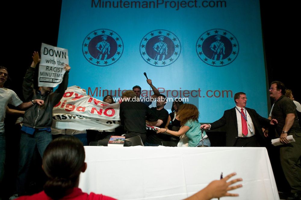 4 October 2006 - New York City, NY - Members of the student organisation the Chicano Caucus of Columbia University storm the stage to disrupt a speech given by Jim Gilchrist, founder of the anti-immigration Minuteman Project organisation, to the College Republicans at the University in New York City, USA, 4 October 2006. Gilchrist had to leave the stage only a few minutes after starting to speak.