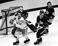 Seals vs Los Angeles Kings, 1975 action, Joey Johnston with Kings Rogie Vachon, Frank St. Marselle, and Neil Komadoski. (photo/Ron Riesterr)