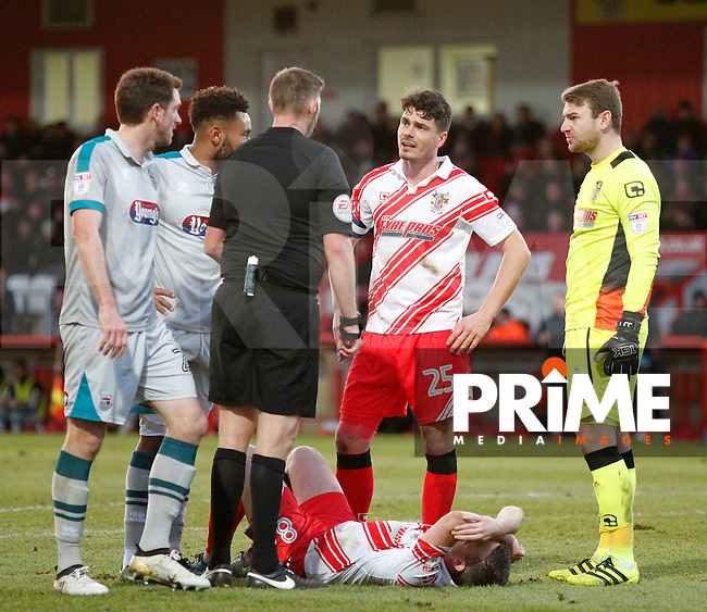 Stevenage's Steven Schumacher lays on the floor whilst Ronnie Henry speaks with referee Brett Huxtable during the Sky Bet League 2 match between Stevenage and Grimsby Town at the Lamex Stadium, Stevenage, England on 28 January 2017. Photo by Carlton Myrie / PRiME Media Images.