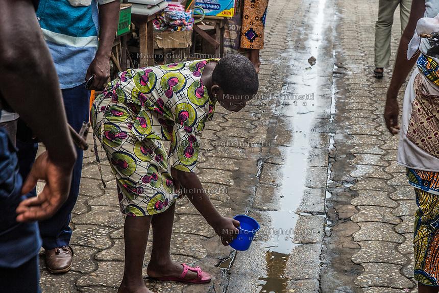 Mercato di Cotonou, una bambina getta dell'acqua