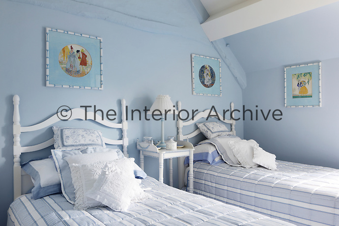 A pale blue guest bedroom with twin beds covered with striped quilts