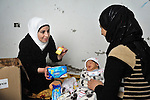 A Syrian refugee woman (right), who asked not to be identified, receives a baby kit for her 17-day old son from Mariam Jiha, a social worker for the Amel Association in Ghaze, a village in Lebanon's Bekaa Valley. The baby kit was provided by the International Orthodox Christian Charities and other members of the ACT Alliance which are assisting Syrian refugees in Lebanon in a variety of ways..