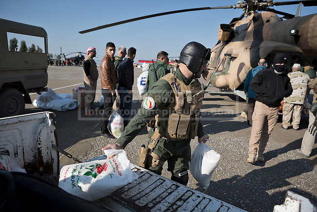 11/12/2014. Fishkhabour, Iraq. Members of the Iraqi-Kurdish security forces load up an Iraqi Air Force Mi-171E Hip helicopter with supplies for Yazidi refugees on Mount Sinjar.<br /> <br /> Although a well publicised exodus of Yazidi refugees took place from Mount Sinjar in August 2014 many still remain on top of the 75 km long ridge-line, with estimates varying from 2000-8000 people, after a corridor kept open by Syrian-Kurdish YPG fighters collapsed during an Islamic State offensive. The mountain is now surrounded on all sides with winter closing in, the only chance of escape or supply being by Iraqi Air Force helicopters.