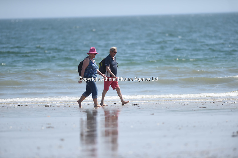 Thursday 25 May 2017<br /> Pictured: A couple take a stroke along north beach in Tenby <br /> Re: People enjoy the warm sunshine in Tenby, , West Wales. Temperatures today are expected to reach the high 20s Centigrade in many parts of the UK, making it one of  warmest days of the year so far