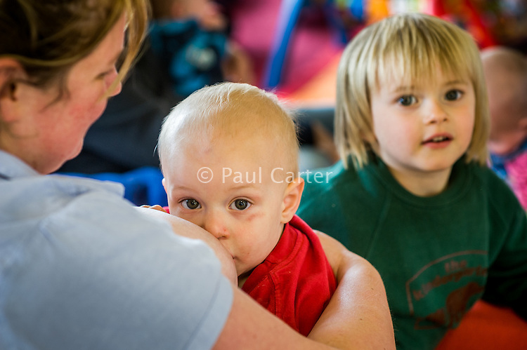 A woman breastfeeding her little boy who is sitting on her lap at a breastfeeding advice and support drop-in centre. His older brother is in the background.<br /> <br /> Image from the &quot;We Do It In Public&quot; documentary photography project collection: <br />  www.breastfeedinginpublic.co.uk<br /> <br /> Hampshire, England, UK<br /> 13/06/2012