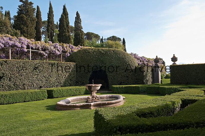 A stone fountain in the centre of the formal garden towards a pergola draped in purple wisteria