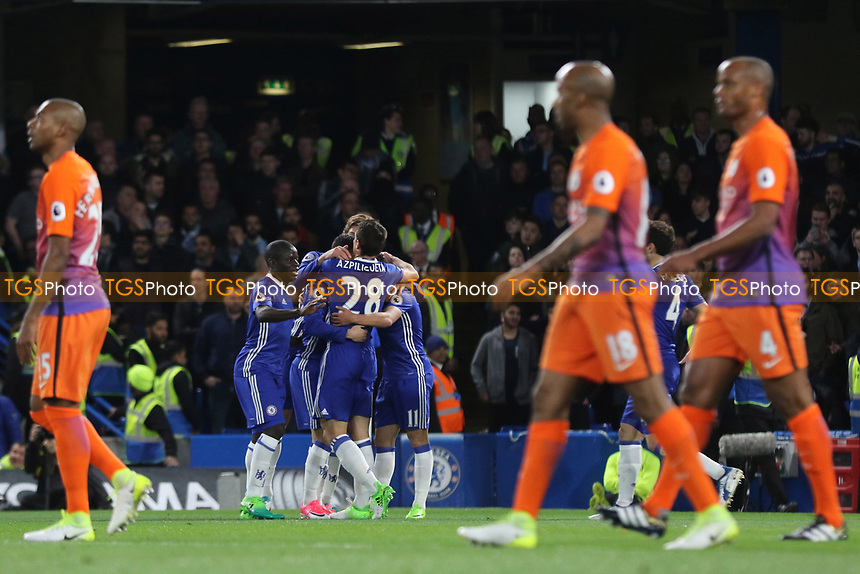 Chelsea players congratulate Eden Hazard after scoring their opening goal as Manchester City players trudge back to the halfway line during Chelsea vs Manchester City, Premier League Football at Stamford Bridge on 5th April 2017