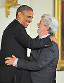 George Lucas, right, hugs United States President Barack Obama, left, prior to accepting the 2012 National Medal of Arts during the presentation ceremony in the East Room of the White House in Washington, D.C. on Wednesday, July 10, 2013.<br /> Credit: Ron Sachs / CNP