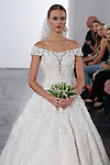 Model walks runway in an off the should dropped waist ball with with beaded Chantilly lace bodice and organza three dimensional floral appliqués from the Dennis Basso for Kleinfeld 2018 Bridal Collection on October 5 2017, during New York Bridal Fashion Week.