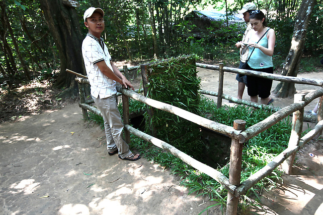"A tour guide demonstrates a reconstructed ""tiger trap"" at the Chu Chi tunnel complex in Chu Chi, Vietnam. Steel or bamboo spikes lined the bottom of the pit and would kill or seriously wound anyone who fell victim to the trap. The device was only one of many ingenious booby traps that Viet Cong soldiers used against U.S. and South Vietnamese troops in the guerilla stronghold. July 2, 2011."