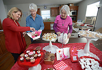 NWA Democrat-Gazette/ANDY SHUPE<br /> Bonny Stitt (from left), Jane Bryant and Jeffi O'Kane, all volunteers with the Friends of the West Fork Library, set up candy and chocolates Thursday, Feb. 8, 2018, for the second Valentine Chocolate Buffet in Library Hall north of the library in West Fork. Visitors are invited to assemble a special Valentine's Day box with chocolates for a $10 donation to the group. The buffet is planned for 10 a.m. to noon Saturday and will feature chocolate items made by more than 40 residents. The Friends are working to fund an addition to the adjacent library in addition to other projects.