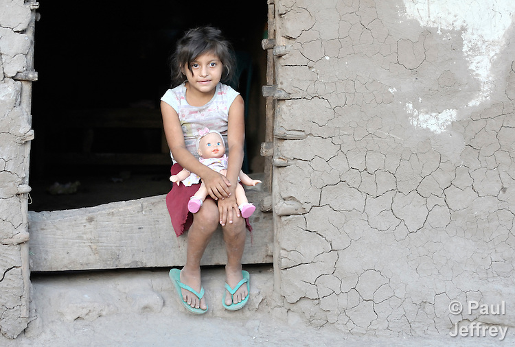 A Honduran girl in the doorway of her adobe house.