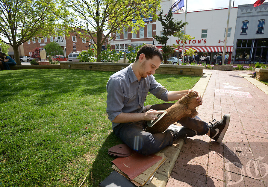 NWA Democrat-Gazette/BEN GOFF @NWABENGOFF<br /> Emerson Sigman, an artist from Chicago, works on his performance piece 'True Grit' on Friday April 22, 2016 on the Bentonville square as part of the inaugural Inverse Performance Art Festival. Sigman began sanding the log Friday afternoon and will continue 'until it's gone.' The festival opened Friday with performers throughout Bentonville and at 21c Museum Hotel and continues on Saturday with events throughout Fayetteville and at Crystal Bridges Museum of American Art in Bentonville.