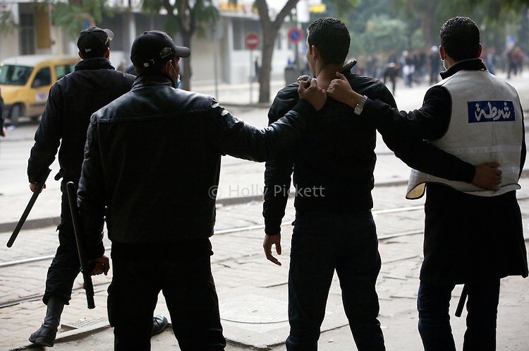 Police detain a protester during demonstrations in downtown Tunis, Tunisia, Jan. 18, 2011. The Tunisian police and army struggled to maintain order in the capital, as thousands of protesters once again filled the streets.