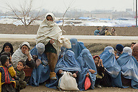 Refugee camp in South West Kabul Afghanistan near Charah Qambar. The refugees were from Sangine in the Helmund province of Afghanistan. They were also a few families from Kandahar. They had fled the fighting between the Taleban and Nato forces. On March 2nd there were chaotic scenes as refugees queued for aid (clothes and blankets) being distributed by an NGO.  Women waiting their turn in the queue.
