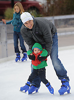 NWA Democrat-Gazette/ANDY SHUPE<br /> Christian Quie of Bentonville skates Saturday, Nov. 21, 2015, with his 18-month-old son, Caden, during the first day of skating at the Lawrence Plaza skating rink in Bentonville. The rink is beginning its sixth year and is open daily through mid-January. Visit nwadg.com/photos to see more from the opening day.
