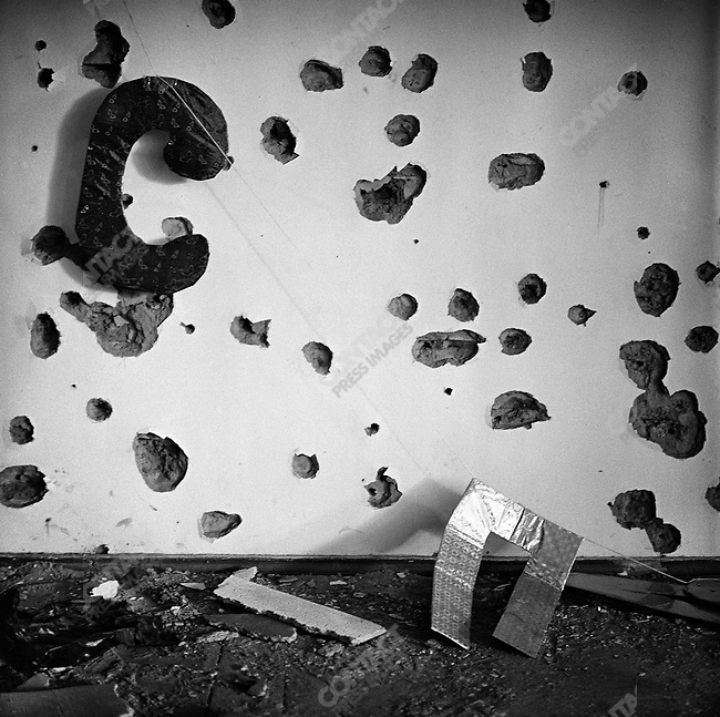"""In the auditorium of school #1 cyrillic letters laying  hanging infront of a mass of bullet holes.  The letters are from the phrase """"S Praznikom"""" which means """"Happy Holiday"""" strung up to welcome children and parents for the first day of school on September first, the day the school was taken by terrorists. Beslan, North Ossetia, September - October 2004"""