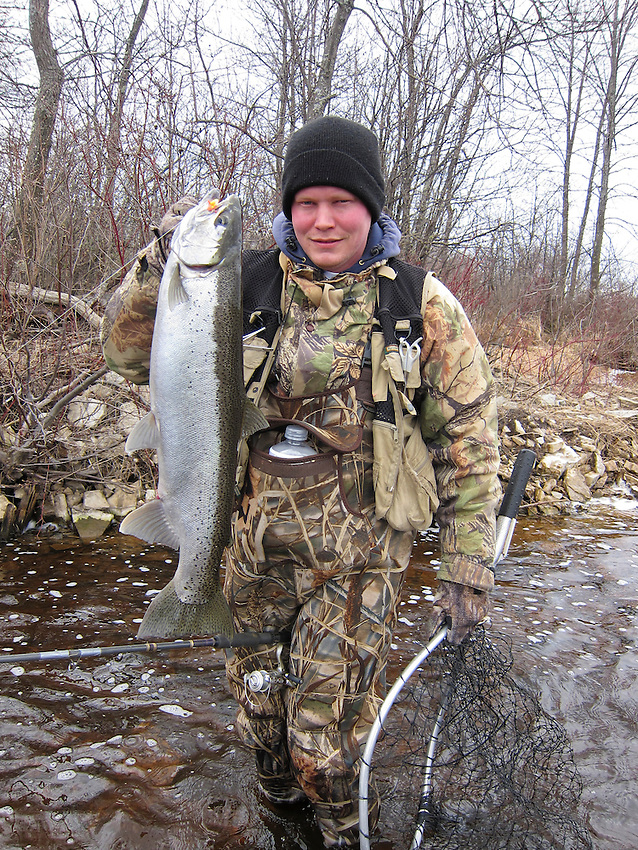 A young man angler fisherman holds a silver steelhead rainbow trout he caught from the Manistique River in Manistique Michigan.