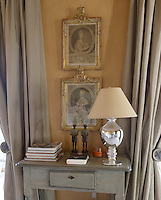 Delicate 18th-century engravings framed in faded giltwood hang above an antique side table in the bedroom