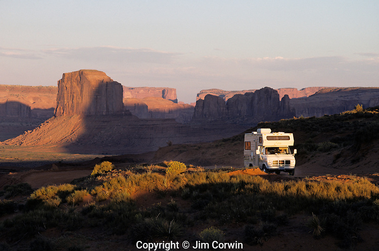 Monument Valley sunset light on rock formations with a recreational vehicle on dirt road Arizona State USA