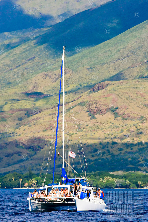 Sailboat of people on vacation hope for whale encounter in coastal waters of Maui.