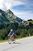 Austria, Vorarlberg, Damuels: mountainbiker at Cheese Route, at background popular resort Damuels at Bregenzerwald | Oesterreich, Vorarlberg, Damuels: Mountainbiker unterwegs auf der Kaesestrasse im Bregenzerwald von Damuels Richtung Au