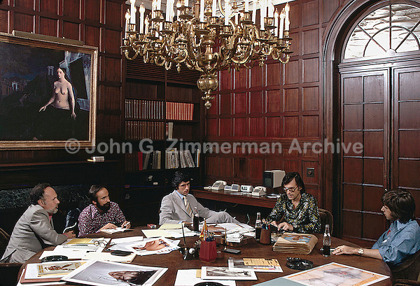 Hugh Hefner (glasses) and Playboy staff review magazine layouts at his Chicago mansion, 1973. Photo by John G. Zimmerman.