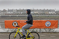 Pictured: A cyclist rides past a banner advertising the game by river Usk in Newport, Wales, UK. Thursday 14 February 209<br /> Re: The city of Newport is preparing to host the FA Cup match between Newport County and Manchester City at Rodney Parade, Newport, Wales, UK.