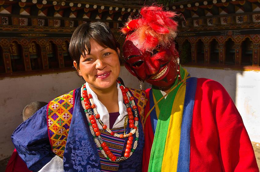 Woman with masked clown, Paro Teschu festival, Paro Dzong Monastery,  Paro Valley, Bhutan