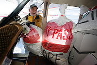 Volunteer pilot Reagan Russey loads his Cessna 180 with musher's food bags at the Willow airport during the first day of flying straw, musher's dog food bags and people food & gear out to checkpoints south of the Alaska Range.  Saturday Feb. 21, 2009  Iditarod 2009