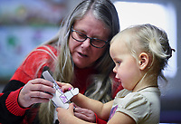 NWA Democrat-Gazette/CHARLIE KAIJO Janet Clauson of Rogers (from left) helps Amethyst Lang, 2, make a paper nutcracker, Monday, December 2, 2019 during the Storytime Express early childhood development program at the Rogers Public Library in Rogers.<br /> <br /> Storytime Express is a traditional storytime for ages 3-5 years. Children read stories, sing songs, do movement rhymes and make a craft. Each week they focus on a different letter of the alphabet. Programs at the library will conclude during the week of Christmas and will resume again after the new year.