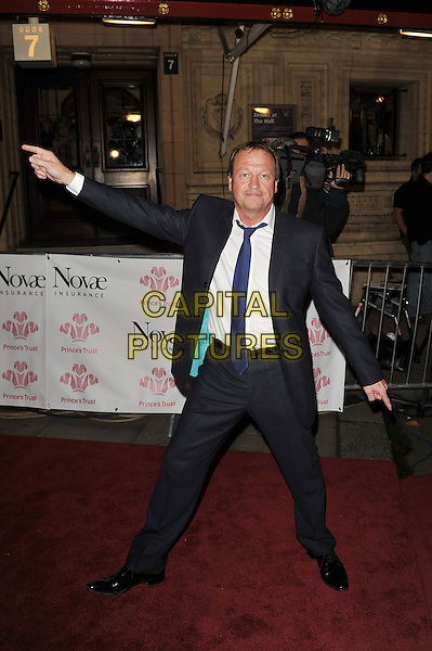 Mark King.'Prince's Trust Rock Gala', Royal Albert Hall, Kensington, London, England. .23rd November 2011.full length black  suit white shirt tie hands arms posing funny gesture blue.CAP/MAR.© Martin Harris/Capital Pictures.