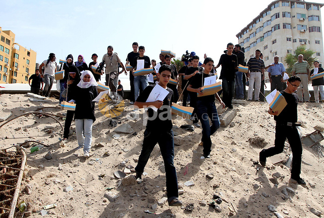 Palestinian youths stand along the shore ready to push paper boats out into the Mediterranean Sea as they rally to demand the lifting of an Israeli blockade on the Gaza Strip, on October 17, 2010, a day after a delegation of the Elders group of retired world figures visited the Hamas-ruled Gaza Strip and called Israeli restrictions on the Palestinian enclave both illegal and an obstacle to peace . Photo by Ashraf Amra