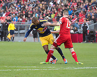 Toronto, Ontario - May 17, 2014: Toronto FC defender Steven Caldwell #13 battles for a ball with New York Red Bulls forward Thierry Henry #14 in the second half during a game between the New York Red Bulls and Toronto FC at BMO Field. Toronto FC won 2-0.