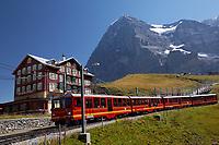 Red rail cars on the Jungfrau railway run past Hotel Des Alps below the north face of the Eiger at Kleine Scheidegg, Bernese Oberland, Switzerland