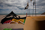 Binh, an employee at STORM Kiteboarding in Mui Ne inflates surf kites on the beach.