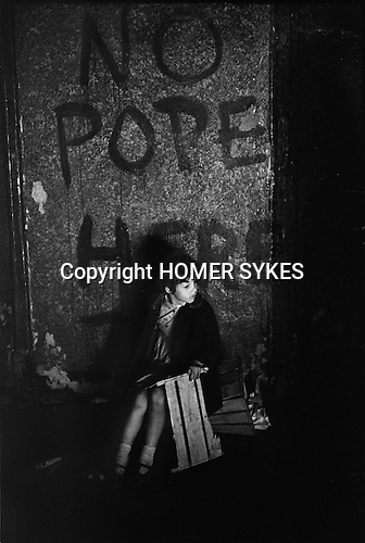 Belfast Orange Day July 1970 Young girl sits under political slogan No Pope Here. She is watching an Orange Day Celebration Bonfire.