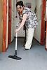 Eastern European working as cleaner hoovering office corridor,