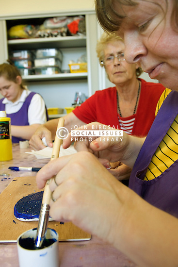 Woman Day Service Officer supervising a service user with learning disability whilst she is mixing paint,