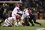 Nyheim Hines (7) of the North Carolina State Wolfpack is tackled by Demetrius Kemp (34) and Grant Dawson (50) during first half action at BB&T Field on November 18, 2017 in Winston-Salem, North Carolina.  (Brian Westerholt/Sports On Film)