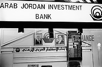 "Jordan. Amman. Arab Jordan Investment Bank. Exchange rates. Portraits of King Abdullah II and his father King Hussein, both dressed as an western business man. His Majesty King Abdullah II bin Al Hussein, is the actual King of The Hashemite Kingdom of Jordan.His Majesty King Abdullah II bin Al Hussein is the 43rd generation direct descendant of the Prophet Muhammad. He assumed his constitutional powers as Monarch of the Hashemite Kingdom of Jordan on February 7th, 1999, the day of the death of his father, the late Royal Highness King Hussein bin Talal (1935-1999), known to his  people as Al-Malik Al-Insan (""The Humane King"").© 2002 Didier Ruef"