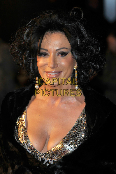 NANCY DELL'OLIO.'NINE' world film premiere.Odeon cinema Leicester Square, London, England. 3rd December 2009.portrait headshot black coat fur gold sequined sequin cleavage low cut dangly earrings smiling .CAP/PL.©Phil Loftus/Capital Pictures.