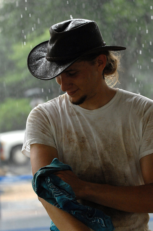 Stephen Browning of Charleston, S.C., washes off with rain water at the Appalachian log cabin exhibit at the Smithsonian Folklife Festival.